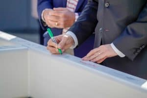Person signing a construction beam, event photography